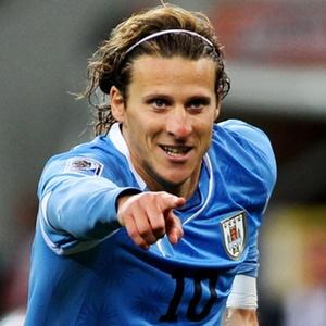 Uruguaio Diego Forlán comemora um gol pela seleção buscando plástico bolha para apertar, no banco de reservas.
